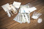 image of drug dealer  - Drugs money and syringes on a wooden background - JPG
