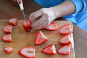 stock photo of hand cut  - Female hand  is cutting strawberries on the wooden table - JPG