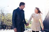stock photo of flirt  - Laughing young couple walking and flirting outdoors - JPG