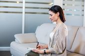 stock photo of psychologist  - Psychologist sitting on the couch and taking notes in the office - JPG