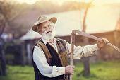stock photo of scythe  - Old farmer with scythe taking a break from mowing the grass - JPG