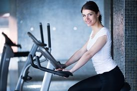 stock photo of cardio exercise  - Woman riding an exercise bike in gym - JPG