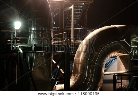 Big industrial pipes view by night with illumination