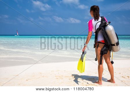 Woman in scuba diving gear on the beach