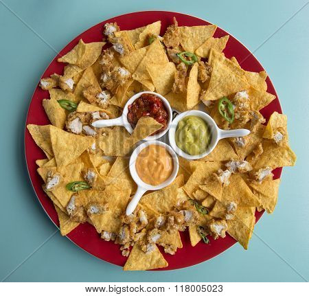 platter of nachos with cheese sauce, guacamole and spicy salsa