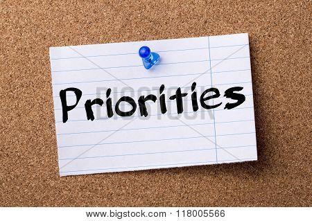 Priorities - Teared Note Paper  Pinned On Bulletin Board