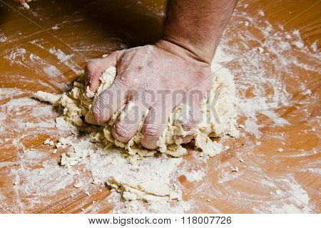 Men's hands knead the dough on the wooden table. The chef prepares the dough for Italian cuisine.