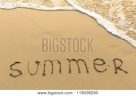 Summer - word drawn on the sand beach with the soft wave.