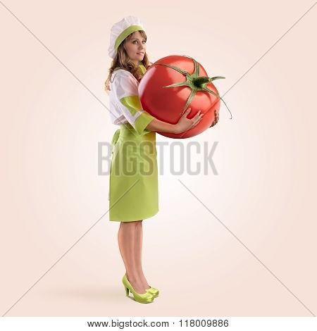 cook girl holding a large tomato
