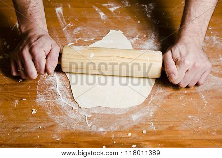 Man's hands rolled dough with wooden rolling pin on the wooden table.