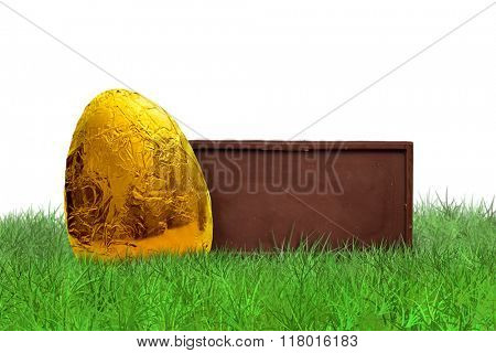 Chocolate bar and golden Easter egg on grass on white background