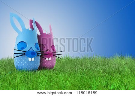 Funny Easter bunny couple on grass on blue background
