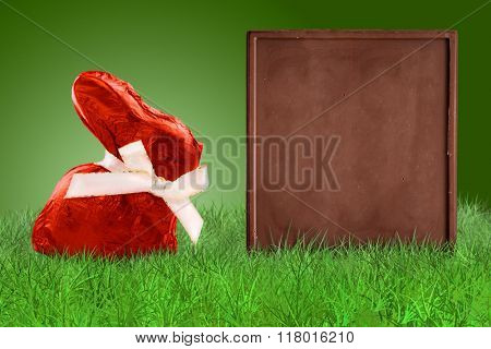 Red Easter bunny and chocolate bas as a board on grass on green background