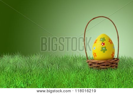 Painted Easter egg in a basket on grass on green background