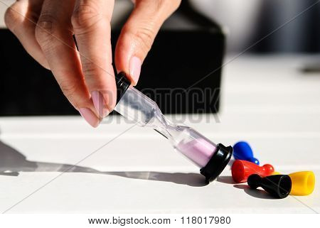 Female Hand Holds Hourglass. Nearby On A Wooden White Table Are Colored Chips: Red, Blue, Yellow, Bl