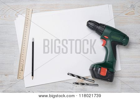 Top view of green drill with bits, ruler and pencil on white blank paper. Wooden DIY workbench, copy