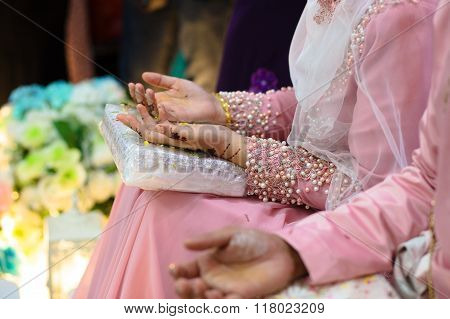 Malaysian wedding ceremony.The background is blurry with the focus on fingers