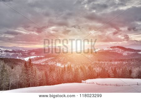 View of sunset in snowy mountains, ski slope
