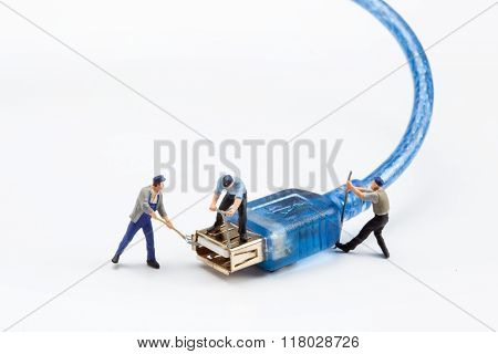 miniature people  - workers fixing a USB plug