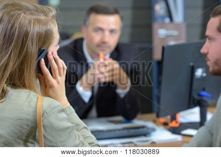 Couple in meeting, lady on telephone