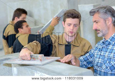 Teacher showing apprentice how to float cement