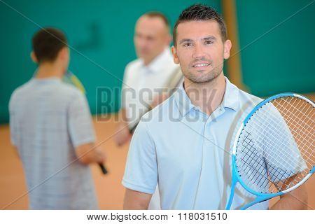 Portrait of man holding tennis racket