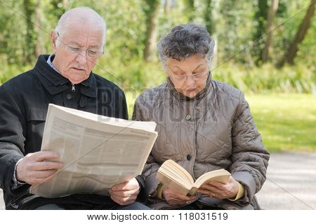 Elderly couple reading outdoors