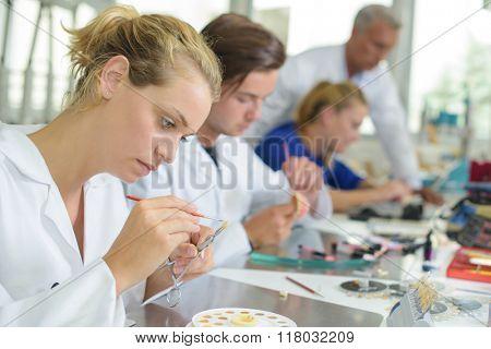 Female technician adding colour to false tooth