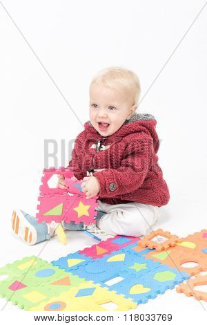 little child baby smiling playing with puzzles warm clothing isolated on white studio shot