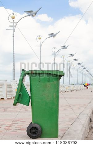 Green dumpster on cement street and electric pole bird