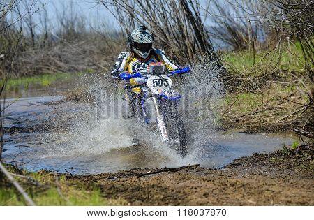 Enduro motorcycle rides through the mud with a big splash