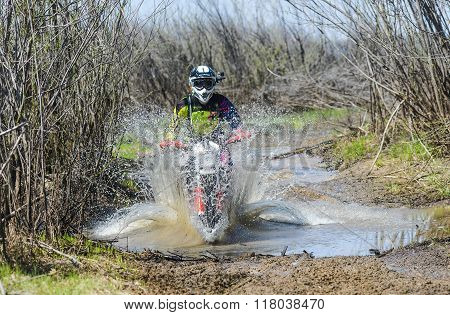 Enduro motorcycle rides through the mud with a big splash