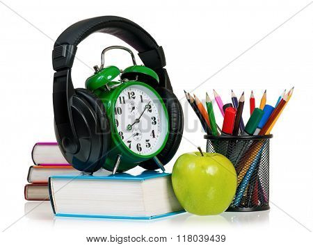 Time concept - alarm clock with books, headphones, pencils and apple