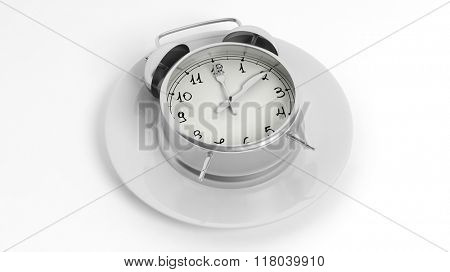 Silver alarm clock with fork and knife pointers on plate, isolated on white background.
