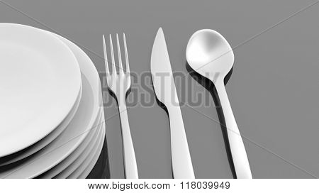 Silver fork, spoon and knife with a stack of plates, isolated on black background.