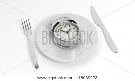 Alarm clock on plate with fork and knife, isolated on white background.