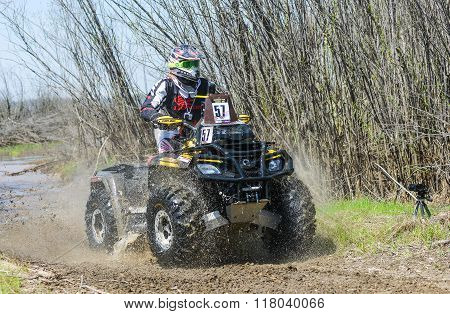ATV rides through the mud with a big splash
