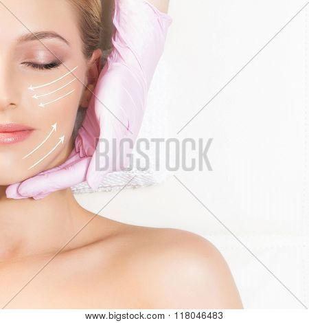 Healthy and young woman is getting massage treatment in a clinic (face lifting concept with the arrows)