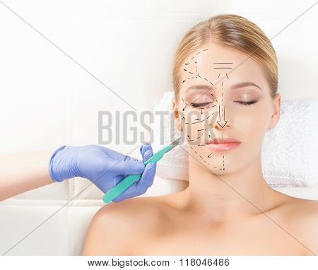 Beautiful woman getting face lifting operation. Drawing arrows and a scalpel over her face. Aging and plastic surgery concept.