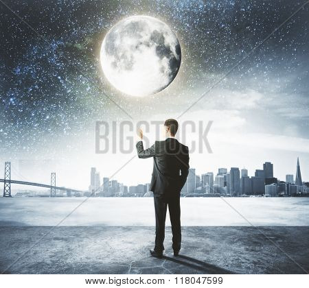 Businessman Holds The Moon Like A Balloon At City Background