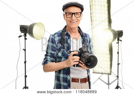 Senior photographer standing in a studio with studio lamps behind him isolated on white background