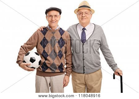 Studio shot of a senior gentleman holding a football and posing with an old friend isolated on white background