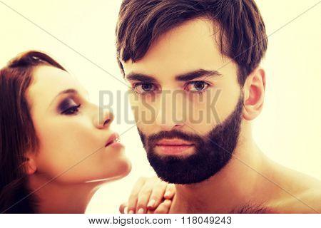 Beautiful woman whispering to man's ear.