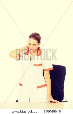 Tired young female doctoror nurse standing behind the desk
