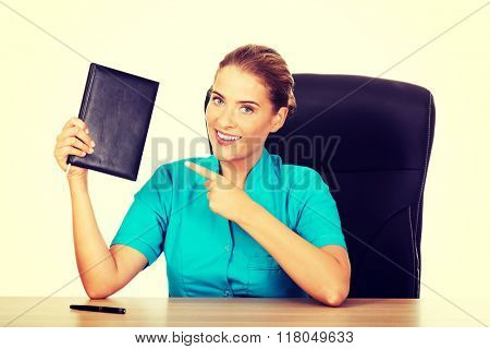 Young female doctor or nurse shows notebook