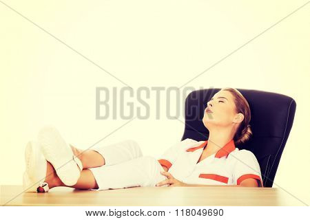 Young tired female doctor sleeping with legs on the desk