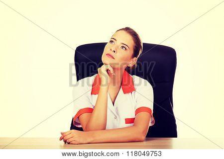 Female doctor or nurse sitting behind the desk