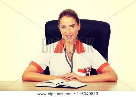 Smile female doctor or nurse sitting behind the desk