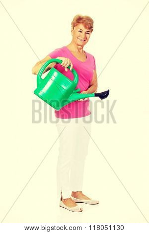 Smiling senior woman with green watering can