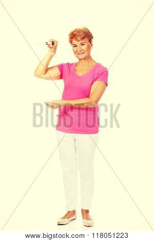 Smiling senior woman shows thermometer